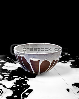Ceramic bowl and spilled milk in black