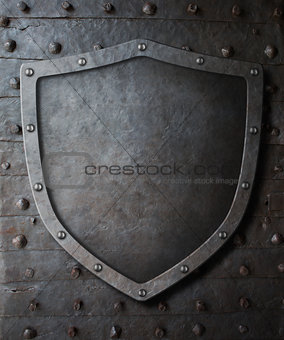 old medieval coat of arms shield over metal door background