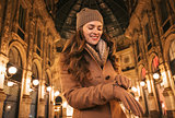 Happy woman adjusting glove in Galleria Vittorio Emanuele II