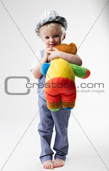 little baby with hat hugging his teddy bear