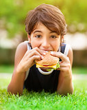 Teen boy eating burger outdoors