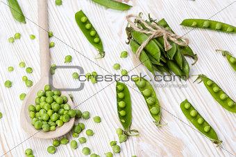 Green peas on wooden desk.
