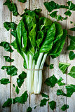 raw chard leaves on a rustic white table