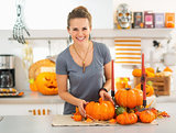 Smiling young woman decorating kitchen for halloween
