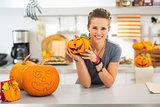 Woman with ceramic pumpkin in halloween decorated kitchen