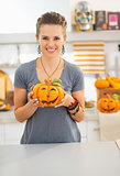 Woman with ceramic pumpkin in halloween decorated kitchen