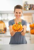 Closeup on woman showing ceramic halloween pumpkin in kitchen