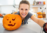 Smiling young woman taking selfie in halloween decorated kitchen