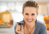 Smiling woman showing spider in halloween decorated kitchen