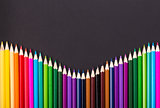 Color pencils arrangement on black