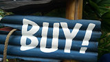 Blue buy sign on wooden block