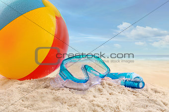 Beach ball and goggles in the sand