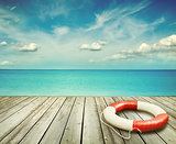 Wood pier with ocean and life preserver