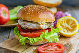 Burger with vegetables, chicken and spicy sauce.