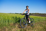 Cheerful beautiful young woman with bike and helmet on field