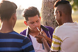 Group Of Teenagers Boy Smoking Cigarette With Friends