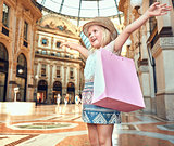 Happy fashion girl with pink shopping bag in Galleria rejoicing