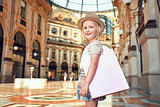 Portrait of smiling fashion girl with shopping bag in Galleria