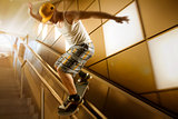 young skateboarder sliding down handrail