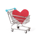 buy love concept, heart in shopping cart on white