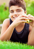 Happy boy eating burger