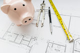 Bank, Compass, Pencil and Measuring Tape Resting on House Plans