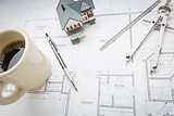 Home, Coffee, Pencil, Ruler and Compass Resting on House Plans