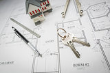 Home, Pencil, Compass, Ruler and Keys Resting On House Plans