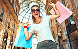 Woman with shopping bags in Galleria Vittorio Emanuele rejoicing