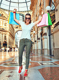Happy fashion woman in eyeglasses with shopping bags rejoicing