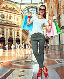 Happy fashion woman in eyeglasses with shopping bags in Galleria