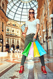 Fashion monger in eyeglasses with shopping bags in Galleria