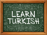 Green Chalkboard with Hand Drawn Learn Turkish.