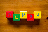 Colorful wooden blocks spelling the word/letters HAPPY