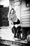 Outdoor shot: smiling young rock girl in shorts, shirt and gaiters stands near train wagon. Black and white