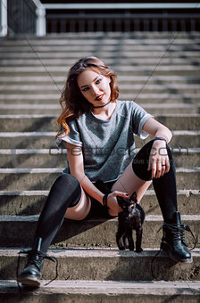 Beautiful smiling rock girl and little black kitten on stairs