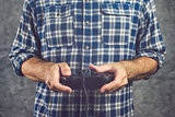 Gamer in plaid shirt playing video game with gamepad