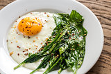 Fried egg with spinach on the wooden table