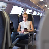 Woman using mobile phone while travelling by train.