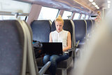Woman travelling by train working on laptop.