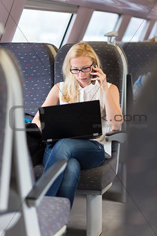 Business woman working while travelling by train.