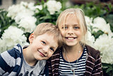 Beautiful blond girl and adorable boy looking at the camera and smiling.