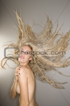 Nude woman with blowing hair.
