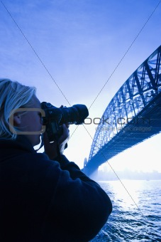 Male teen photographing bridge.