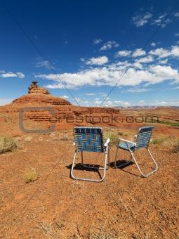 Lawn chairs in desert.