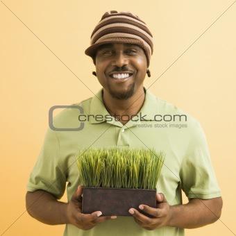 Man holding plant.