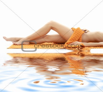 long legs of relaxed lady with orange towel on white sand #4