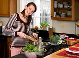 Young woman cooking healthy greens.