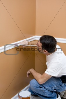 Painter painting trim around doors & windows
