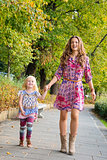 Full length portrait of mother and daughter walking at the park